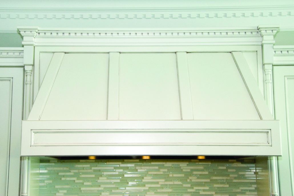 Detailed range hood with pillars and crown moulding